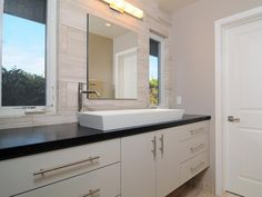 HGTV presents a modern neutral bathroom with single vanity, white rectangular vessel sink, stone wall tiles, black countertop, and white drawers and cabinets.