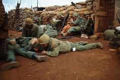 20 Feb 1968, Khe Sanh, South Vietnam --- U.S. Marines lie prone on the ground in sandbagged trench as they take cover from Communist mortar fire.