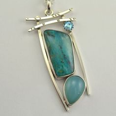 This stone pendant with its elegant open metalwork design has a lovely Asian feeling to it. The gently curving wires capture the collection of stones in a temple door motif. This arty pendant packs a lot of look into its small size. Certain to attract admirers. Beautifully boxed for gift giving.  The stones are Peruvian opal, blue chalcedony and Swarovski crystal. The metal is sterling silver. The pendant measures 1 3/4 tall by 3/4 wide. It is finished with a sterling chain which extends…