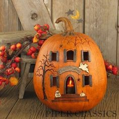 """Our Ghoulish Greetings - Lit House Pumpkin is perfect for Halloween and comes with an electric candle & bulb to illuminate the carvings on pumpkin. Includes flicker bulb (5-watt max.) and 6 foot cord. Size: 12"""" High x 9 3/4"""" Diameter. Resin, Made in America."""