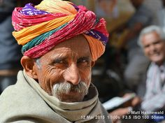 https://flic.kr/p/MBfTZf | 2015-03a Colourful Rajasthan (10) | Closeup street portrait (outdoor headshot with a second person in the background) of an elderly Indian man with fancy, colourful Rajasthani turban aka pagari and grey cowboy moustache; Jaisalmer, Rajasthan, India. More context: matthahnewaldphoto.blogspot.ca/2015/03/tying-rajasthani-p..., konniandmatt.blogspot.ca/2015/03/02-mar-14-mar-2015-jaisa....