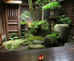 Shady serenity in this Japanese garden. Lots of mossy stones, a water feature and a beautiful deck