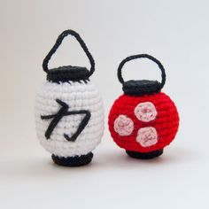 """These little amigurumi lanterns are based on the paper lanterns seen so often in Japan. The round red lantern is decorated with three cherry blossoms and the tall white lantern features the kanji character for """"strength."""""""