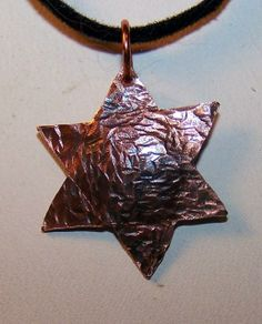 Hammered Copper Star of David, with the center domed outward slightly.  The hammering was done to symbolize the struggle of the Jewish people through the ages.  The piece measures 15 mm point to point.  Made with 18 gauge copper sheet, then antiqued with Liver of Sulphur, then protected with Krylon Acrylic spray.  Available at: https://handmadeartists.com/shop/rasmussengems