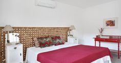 Quarto de casal com papel de parede em cabeceira da cama e cores claras na decoração
