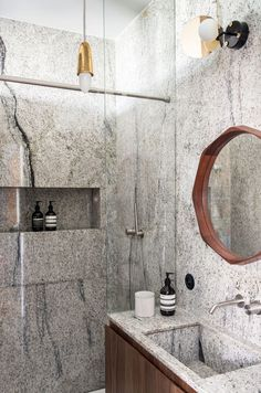 Marble shower, modern mirror, and brass light fixtures in French bathroom