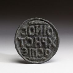 """A byzantin commercial stamp commands people to """"drink good wine."""" 6th to 8th century Bronze"""