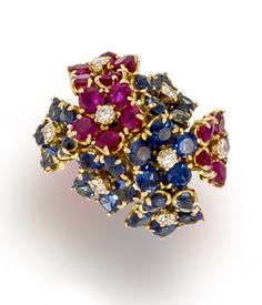 """A sapphire, ruby and diamond ring, Van Cleef & Arpels  of """"Hawaii"""" design, centering floral clusters of circular-cut sapphires and rubies each with round brilliant-cut diamond stamen; signed VCA for Van Cleef & Arpels, with signed pouch; mounted in eighteen karat gold"""