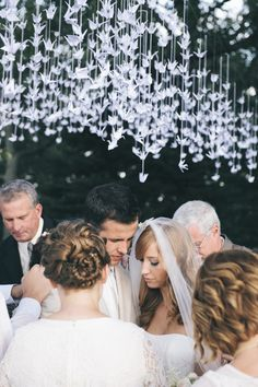 Sometimes something as simple as a layer of paper cranes strung around a ceremony spot can make all the difference in the world. It takes this backyard affair from beautiful to seriously breathtaking upon first glimpse of those white wings.