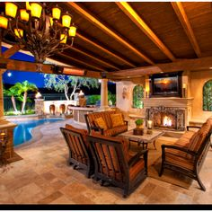 Outdoor entertainment area with fireplace and wooden beams. OC Living