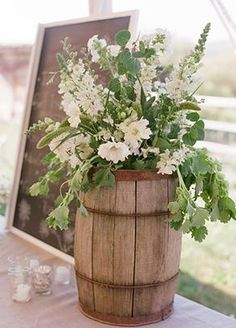 Floral arrangement in a wooden barrel, perfect for a rustic wedding