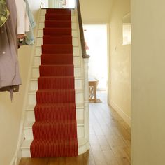 """""""Fit a colourful stair runner.Create a warm first impression in your hallway with a cheerful red wool stair runner on painted white stairs. Go for a tonal red stripe rather than a multi-coloured design to make a sophisticated style statement. Hallway Carpet Runners, Carpet Stairs, Stair Runners, Stairway Lighting, White Stairs, White Hallway, Staircase Design, Staircase Ideas, Hallway Ideas"""