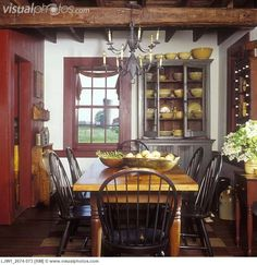 EARLY AMERICAN DINING ROOM WITH WOOD TRIM IN CRANBERRY PAINT.