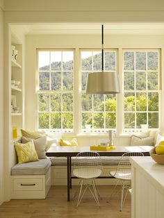 Ken Linsteadt Architects  Built-in banquette with ticking stripe cushions, canary yellow pillows, black dining table, wire chairs, drum pendant, white kitchen island with marble countertop, sink in kitchen island and glass pendants.
