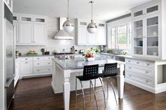 Hood Contemporary Vintage - Kitchen Design Designer: Jane Lockhart Jane Lockhart Interior Design, Toronto, ON Photo: Brandon Barré Photography Story: Maple cabinetry features wide-railed shaker doors and simple crown molding. The large furniture-style island is unobtrusive with an open front and decorative legs. A super white granite slab top offers a stunning focal point and complements gray quartz countertops. White marble slabs comprise the backsplash tile. An integrated china cabinet...