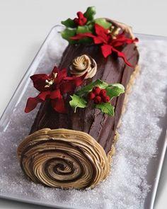 Rollo navideño con pan esponjoso de chocolate con relleno de chocolate oscuro con frambuesas y con hermosa decoración.