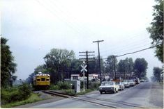 Sperry car 123 looking for track defects, is about to cross Carling Avenue (Highway 17) west of Britannia, and about to enter the stiff Nepean grade. This was on August 8th, 1965, 2 years before track abandonment of the Carleton Place Subdivision which was August 28th, 1967. The right of way is now a bike path. Look at all those old cars! FINA gas station in background. Carleton Place, Ottawa Valley, Bike Path, Gas Station, Sperry, Old Cars, Paths, Abandoned, Trains