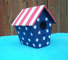 This is a handmade wood bird house that was painted with Acrylic paint. It measures 6.25 inches tall, 5.5 inches wide, and 5.5 inches deep. It is constructed of 1 inch pine board, wood glue, and brads. The roof and floor of the house have been milled down to 1/4 inch. The entrance hole measures 1 1/4 inches. I painted it to resemble the American Flag, with red and white stripes and starts on a navy blue background. This would make a perfect 4th of July gift for the house or garden. ...