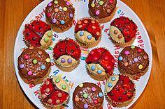 Weiße Kouvertüre mit roter Lebensmittelfarbe einfärben, Muffins bestreichen, mit dunkler Kouvertüre die Konturen ziehen