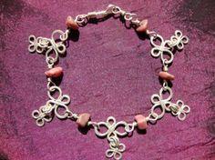 Pulsera con piedras rosa y detalles de flores