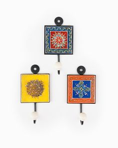 """Jasmine Wall Hooks.   This set of three wall hooks is hand-painted on mango wood, set in a metal frame with metal hooks.    Approx. Measurements: 3"""" x 3"""".   Materials: Metal & painted mango wood.  Colors: Yellow, white, black, red, blue & green.   Made by Empowered Artisans in India.  #compassionatepam facebook.com/compassionatepam. $38"""