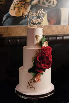 Glamorous red and gold wedding cake with live roses and gilded leaves
