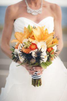 Wedding Bouquet: navy thistle, David Austin garden roses, orange ranunculas, orange dahlias, orange tiger lilies