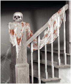 use old skeleton and gauze (yes, from your first aid kit) or cheesecloth and fake blood for a creepy staircase decoration