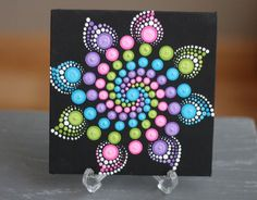 Hand-painted Mandala on a 6x6 canvas. Painted with high-quality acrylic paints, with a gloss finish for protection. Every dot is hand painted without the use of a stencil or template so no two are alike! Plastic stand in picture not included.