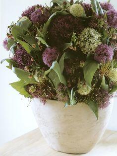 Arranjo de flores lilas em vaso de ceramica