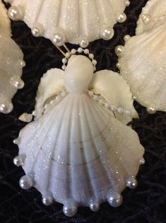 Sea Snow Angels are handmade here at Sea Things in Ventura CA. Each Angel has a Beautiful White Scalloped Seashell. Arms are Pearl lines with a tiny Seashell. Her face is a white moon snail. The Angel