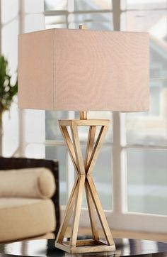 A stylized, geometric hourglass silhouette defines this statement-making table lamp crafted with a caged metal base in gold and topped with a squared-off shade.