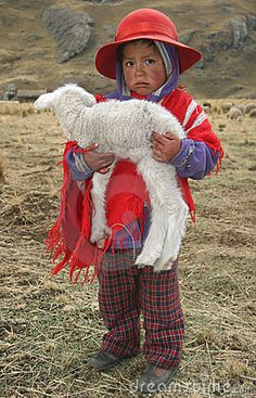 People of Peru and this person is holding a little lamb.