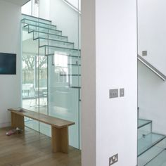 Hallway with glass staircase | staircase is made entirely from glass sheets | interesting way to welcome light into your home