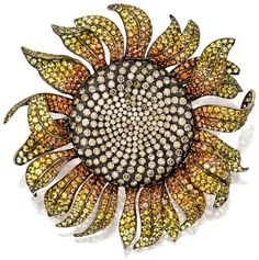 Sunflower brooch by Michele della Valle. The whimsical sunflower set to the centre with brilliant-cut brown diamonds together weighing approximately 19.65 carats, to petals set with circular-cut yellow and orange sapphires together weighing approximately 47.75 carats, mounted in titanium and 18 karat yellow gold