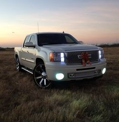 """2009 Pearl white SLT GMC Sierra on 26"""" KMC Slide with a Denali front conversion bumpers painted to match factory Cadillac escalade mirrors, 6k high-low & fog lights HID conversion, rear 2"""" drop for a level look, front switchback led turn signals and full LED taillights smoked front GMC emblem painted to match"""