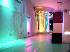 White sensory room with LED, mats, bubble towers. Designed by Roompa.