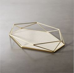 Shop prisma geometric storage catchall. Delicate brass-plated wire sculpts deconstructed diamond-like facets grounded by soft linen lining at the base. We love it for storing jewelry at night. Also lovely as a decorative tray.