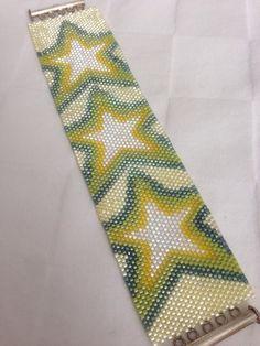 Ce bracelet est fait à l'aide de perles de rocaille delicas en tissage Peyote. Le motif est une conception originale de trois gros cristal scintillant étoiles décoré par jaune transparent, vert chartreuse et aqua. Le fond est d'un jaune très pâle. Se ferme avec un fermoir en argent diapositive. Il mesure 6,25 pouces de long et 1 7/16 pouce de large.
