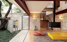 Ao quebrar as paredes, os arquitetos da Apiacá encontraram tijolos de boa qualidade. Eles, então, misturaram os cacos ao concreto. A ideia trouxe conforto visual e térmico tanto para a sala como para a área externa, que pode ser totalmente integrada