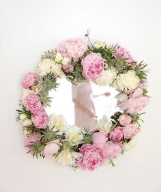 cover a mirror with flowers for lovely decor for a party or bridal shower. i just wish fake flowers were so pretty or i'd make one for my bathroom.