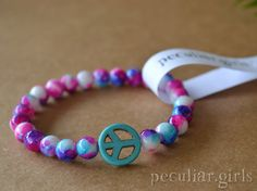 Handmade Peace Sign beaded bracelet on stretch cord. Size: Womens Regular Glass beads speckled and spotted (tie-dye style) with calming pinks,