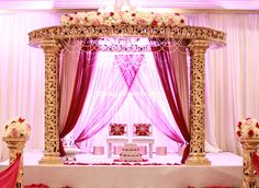 Round Gold Mandap with Mauve and Maroon draping, crowned with flower garlad by iDesignEvents.com