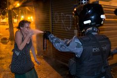 A military police pepper sprays a protester during a demonstration in Rio de Janeiro, Brazil, Monday, June 17, 2013. Protesters massed in at least seven Brazilian cities Monday for another round of demonstrations voicing disgruntlement about life in the country, raising questions about security during big events like the current Confederations Cup and a papal visit next month. ((AP Photo/Victor R. Caivano)