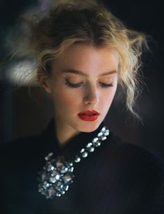 frizzy hair, red lips and oversized necklace.
