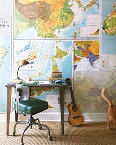 "Renner repurposed vintage roll-up maps as wallpaper on one side of her sons' room, opposite. Other walls are covered in cork so Thompson and Pace can pin up whatever they want. ""They have lots of artwork, awards, and memorabilia they like to display,"" Renner says. The desk came from an office-supply salvage sale."