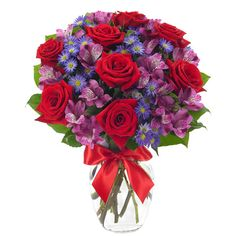 Send a mixed flower arrangement. Delivered with red roses, blue flowers and purple alstroemeria in a keepsake glass vase with decorative red ribbon.