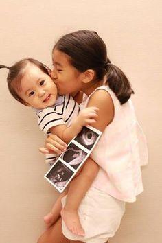 恭喜賈靜雯再度懷孕,大女兒梧桐妹抱著咘咘,手上還拿著寶寶超音波照片。(圖擷自臉書)