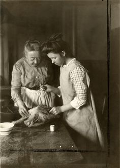 Photo of two women preparing a turkey, 1915..