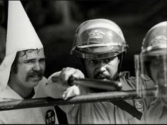 A black policeman protects a KKK member, as protesters were closing in on them in at a rally in Austin, Texas, 1983